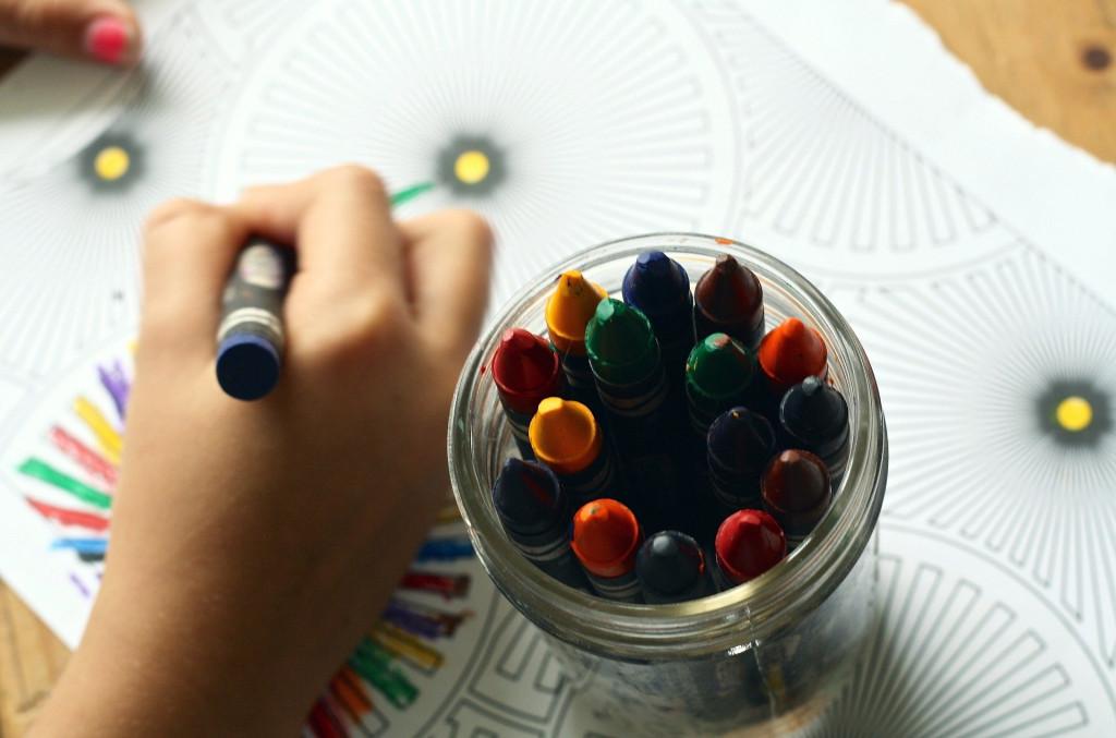 Kinderhand malt mit Buntstift, daneben steht ein Glas mit Wachsmalstiften: Quelle Pixabay